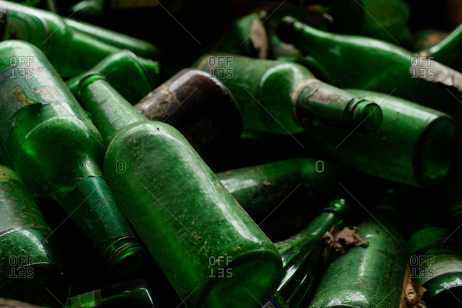 Reusable material. Close up view of dirty green glass bottles prepared for recycling