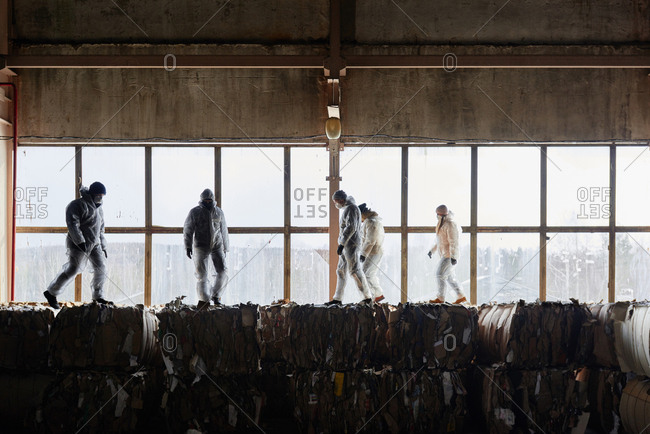 Waste sorters in protective wear walking on top of compressed cardboard blocks at garbage recycling plant