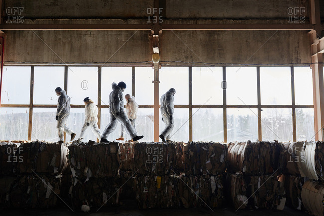 Waste laborers in protective uniform walking on top of compacted cardboard bales against large window at waste recycling plant