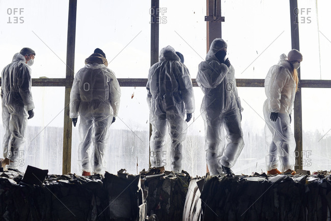 At garbage recycling plant. Conceptual shot of waste operatives in protective uniform standing on bales of compressed cardboard against large window background