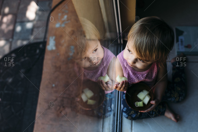 Toddler sitting against a sliding glass door eating honeydew melon