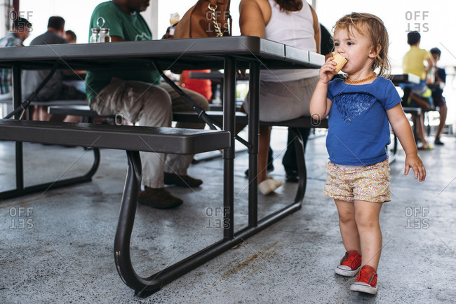 Toddler girl in shorts eating an ice cream cone at an outdoor restaurant