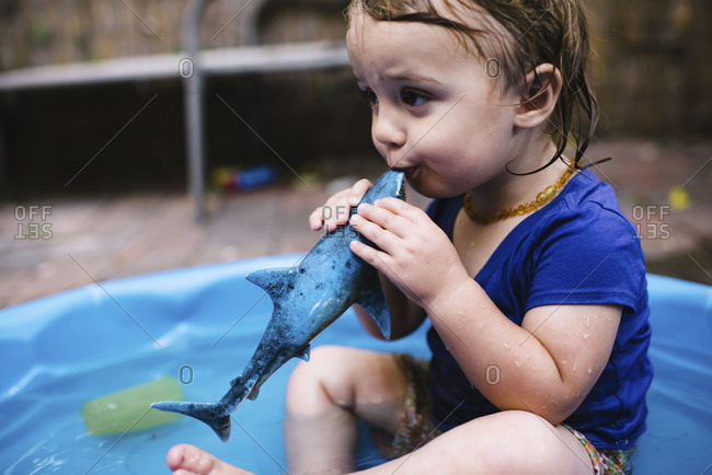 Toddler girl sitting in kiddie pool playing with a plastic toy shark