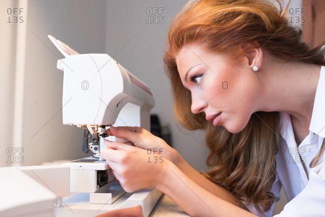 Woman setting sewing machine needle