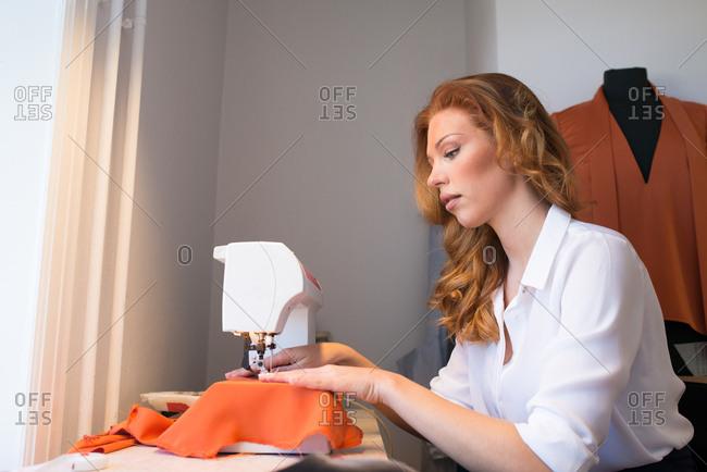 Woman sewing in trendy workshop