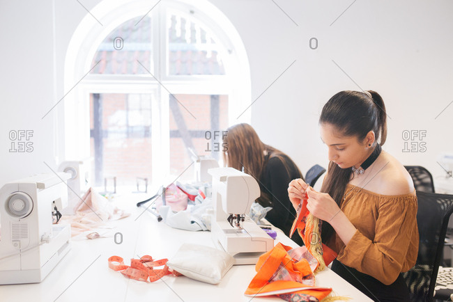 Two women sewing in a studio