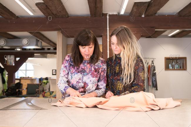 Women with fabric in design studio