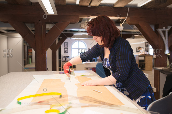 Woman cutting out pattern in workshop