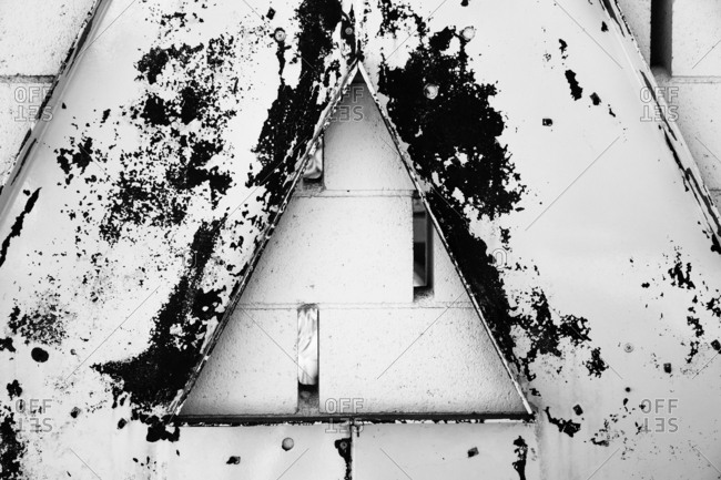 Distressed metal triangle shape over a cinderblock building