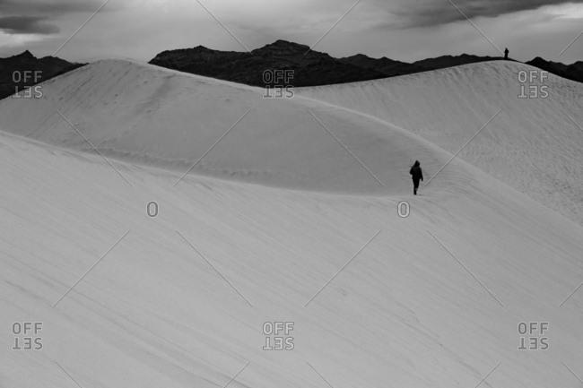 People walking across sand dunes toward mountains