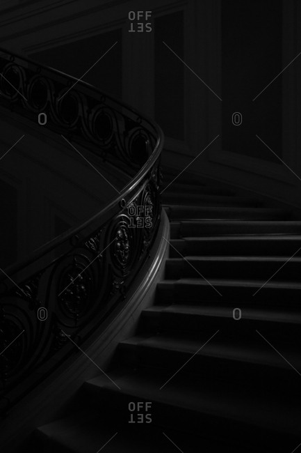 Dimly lit curving staircase with a carved wooden banister