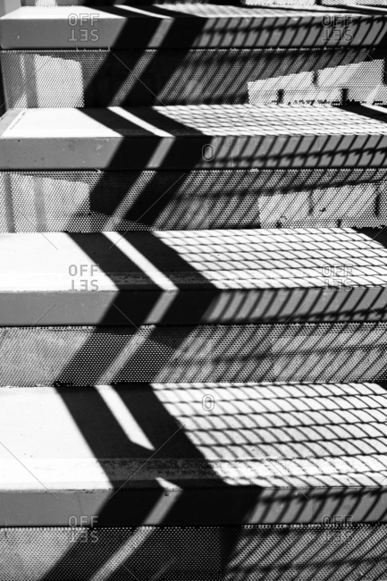 Railing casting a chevron-shaped shadow on a flight of steps