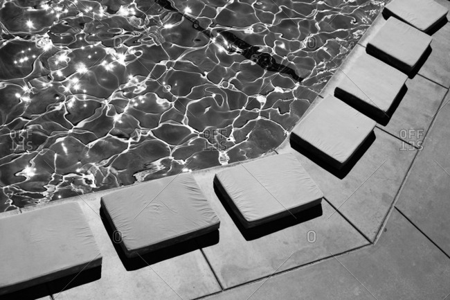 Rectangular cushions lining the edge of a poolside