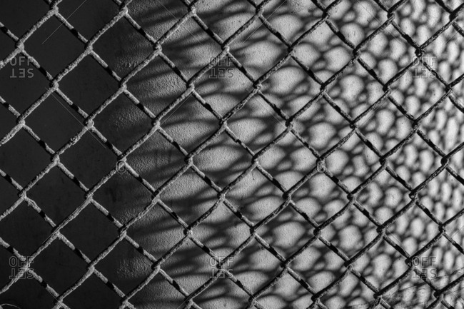 Diamond patterned chain link fence wrapping around concrete