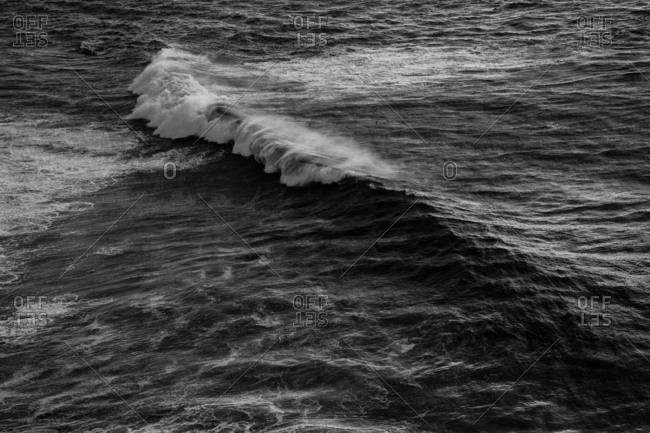 Ocean wave cresting on a rippled water surface