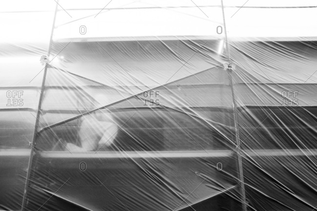 Person kneeling on scaffolding behind protective plastic in front of a building