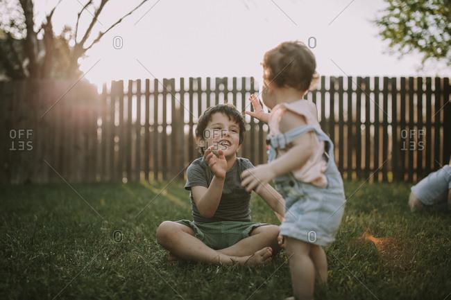 Toddler girl high fiving boy in yard