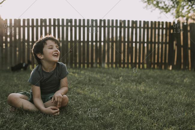 Laughing boy sitting in summer yard