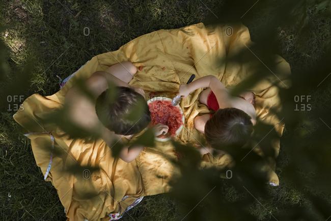 Boys eating a watermelon in yard