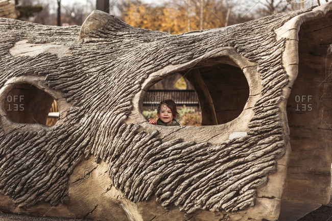 Girl in log-shaped play tunnel