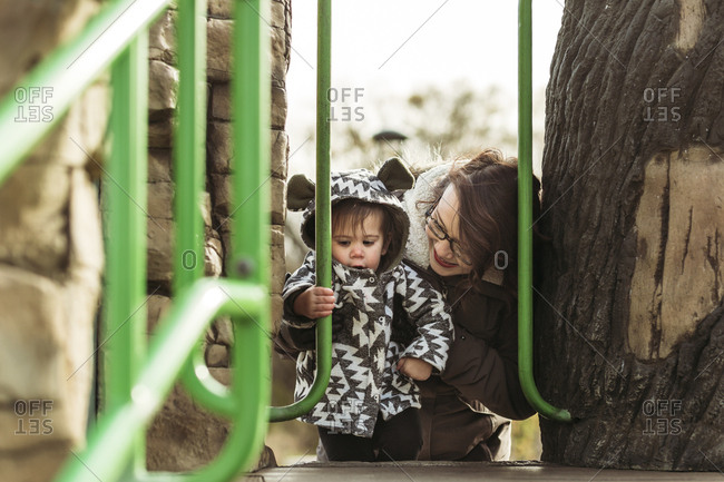 Mom helping girl climb in playground