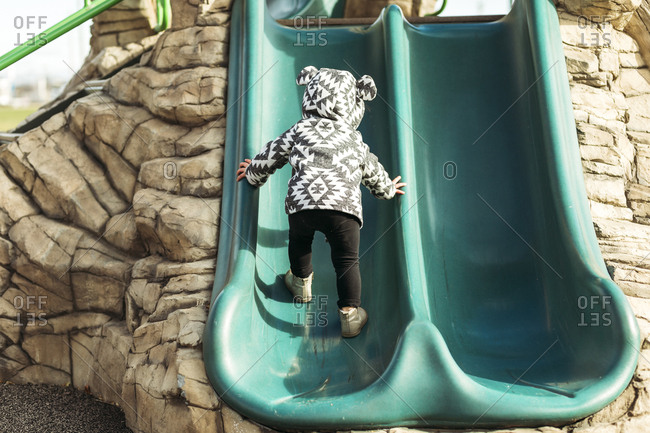 Little girl climbing up playground slide