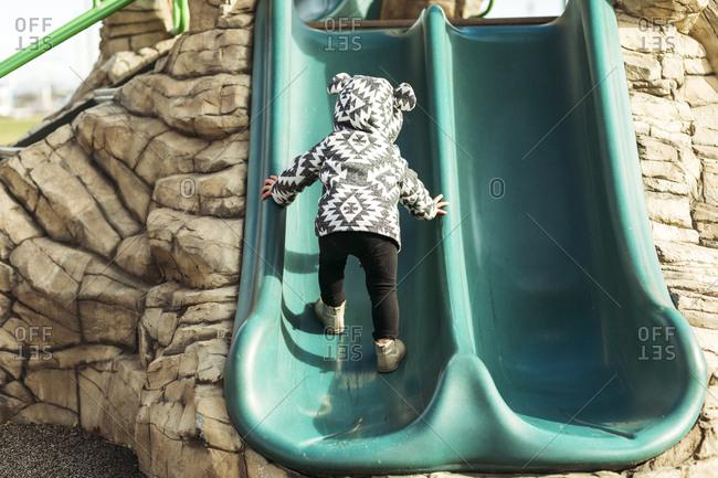 Little girl climbing up playground slide