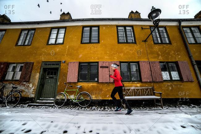 Woman jogging outside historic building in�Copenhagen�in winter
