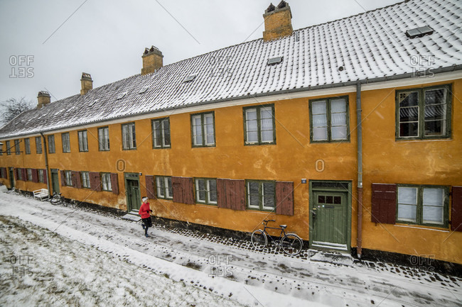 Woman jogging outside historic building in Copenhagen in winter