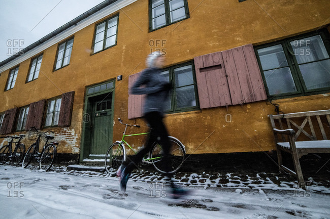 Woman jogging outside historic building in�Copenhagen�in winter with blurred motion