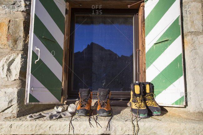 Two pairs of hiking boots dry in the sun on stone wall by window