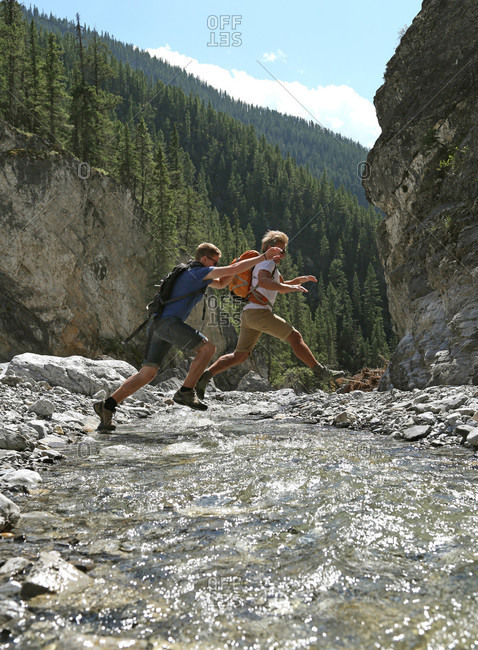 Father and son jumping across mountain river