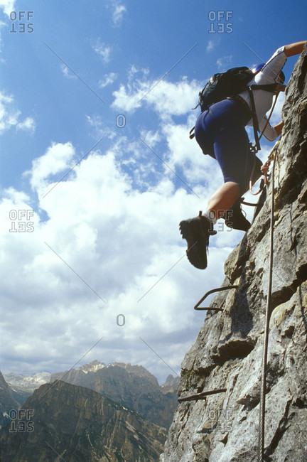 Mountaineer climbing Via Ferrata on mountain ridge