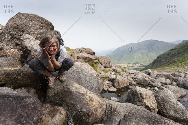 Female hiker splashes water on herself from stream