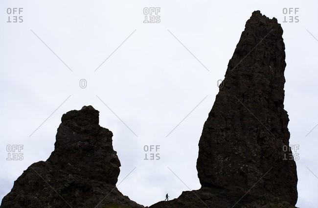 Walker silhouetted between famous rocks