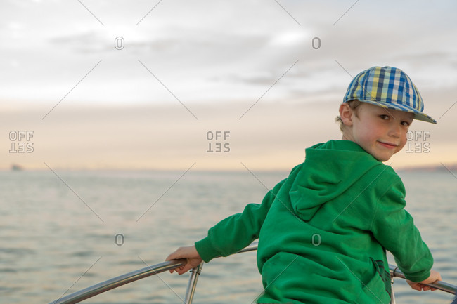 Portrait of young boy on prow of boat