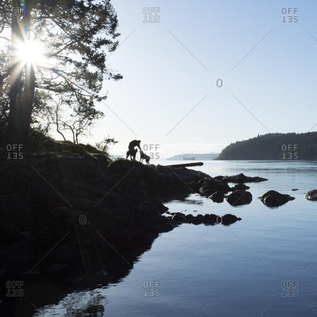 Man descends coastal rocks with dog