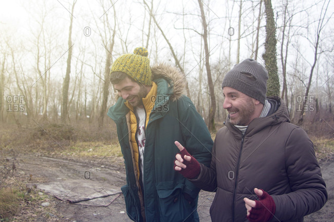 Two Male Friends Chatting While Walking In The Forest