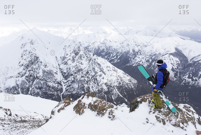 A Skier Stands On A Rocky Mountain Overlooking The Andes Mountains From Cerro Cathedral In Argentina