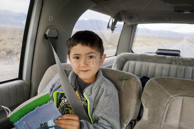 A seven year old boy sits and reads in a suburban on a road trip across Nevada.