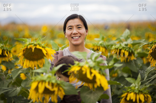 A Japanese American Mom stands in the middle of a field while carrying her 1 year old baby through a field of sunflowers.