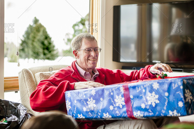 A grandfather opens a gift on Christmas morning.