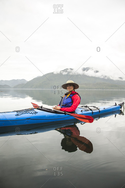 A woman in a blue kayak floats on calm waters under a cloudy sky.