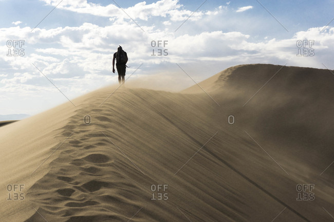 A hiker walking a ridge line in the sand dunes