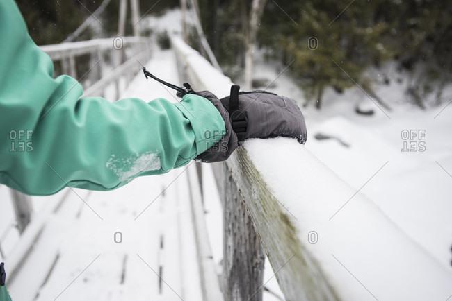 Person hiking across footbridge in winter