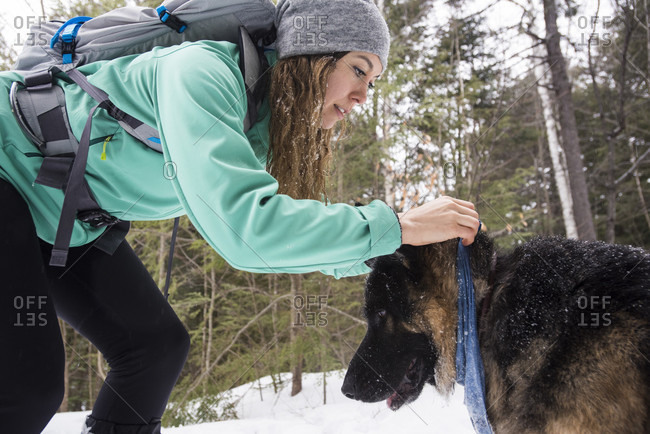 Woman and dog getting ready for hiking in woods in winter