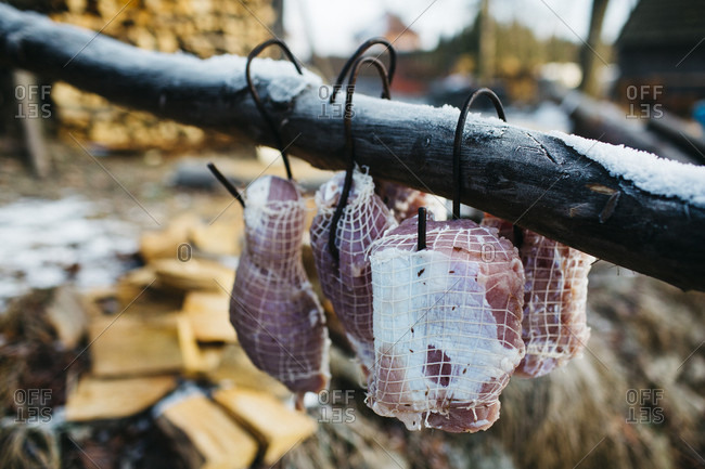 Meat is trussed and hangs from hooks as it is prepared for the smoker