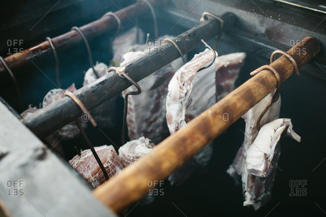 Trussed meat hangs from hooks in a smoker