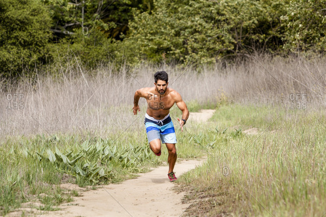 Fit male runner sprinting on warm sunny day