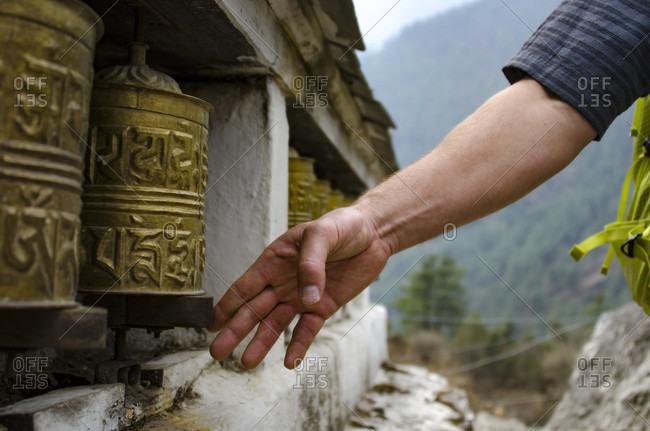Man spins a Tibetan Buddhist prayer wheel along trail to Mount Everest in Sagarmatha National Park